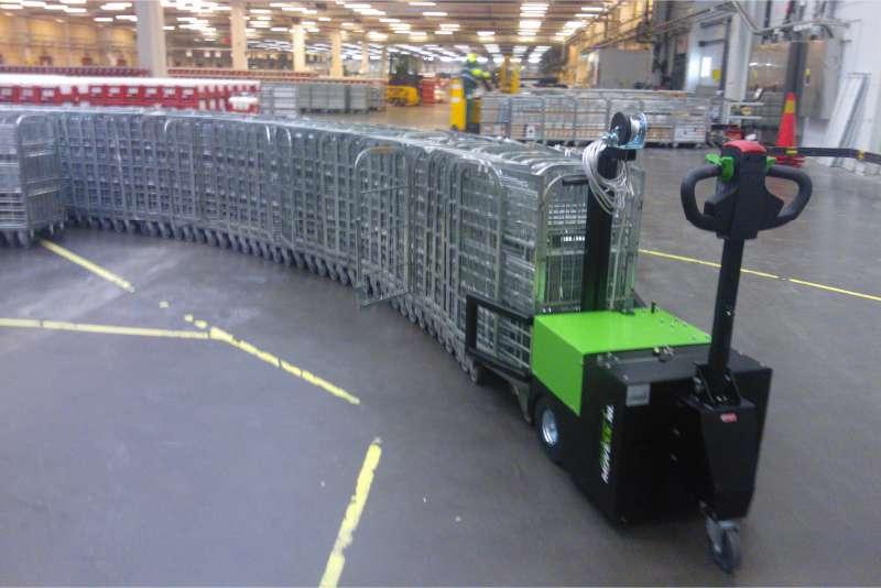 elektrický ručně vedený tahač t3500 s push modulem tlačí celou řadu přepravních klecí ve skladu