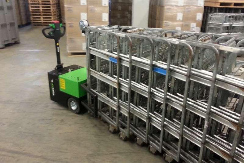 elektrický ručně vedený tahač t3500 ve skladu tlačí před sebou složené přepravní klece pomosí push modulu