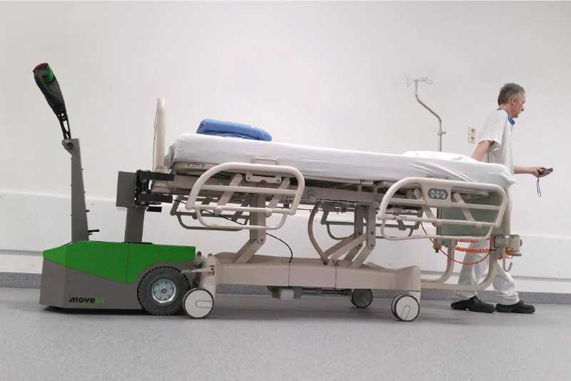 ručně vedený elektrický tahač bm500r-ffc zdravotnický personál ovládá tahač pomocí dálkového ovládání a veze prázdné nemocniční lůžko v nemocnici