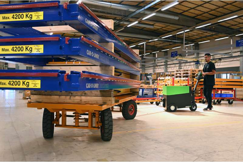 elektrický ručně vedený tahač t6000 manipuluje těžký přívěsný vozík naložený materiálem z výroby