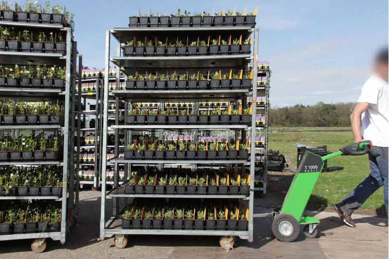 ručně vedený elektrický tahač movexx t1000 basic táhne několik policových přepravních vozíků