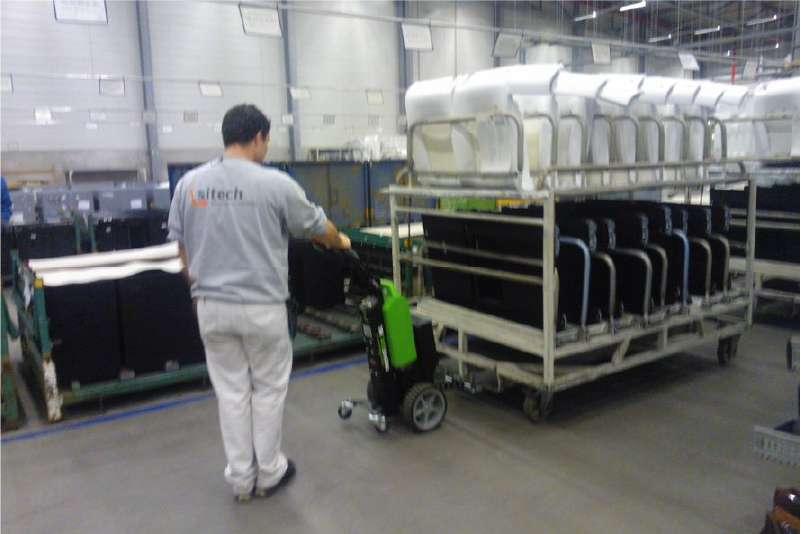 ručně vedený elektrický tahač t1500 manipuluje přepravní vozík s hotovými výrobky v průmyslové výrobě
