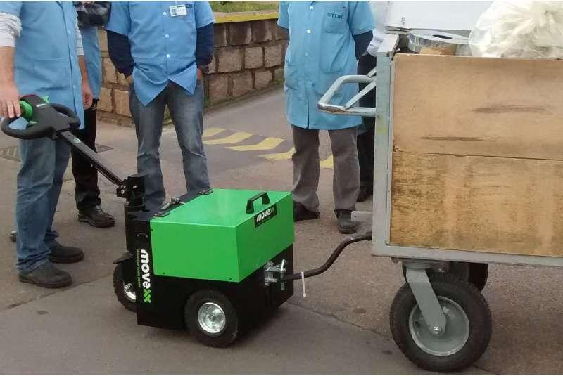 elektrický ručně vedený tahač t2500 připojený pomocí oje k valníku s těžkým nákladem