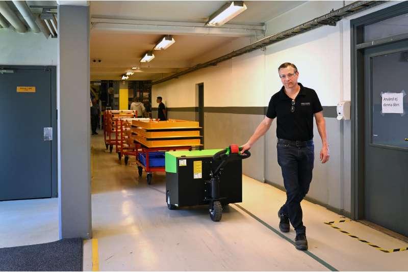 elektrický ručně vedený tahač t6000 veze těžkou tažnou soupravu přepravních vozíků ze skladu do výroby