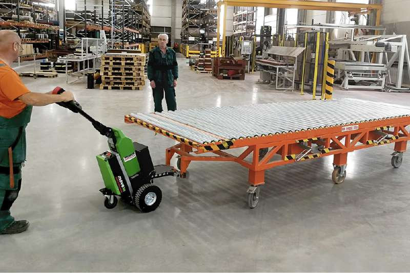 ručně vedený elektrický tahač t1500 přesouvá těžký dopravník na kolečkách