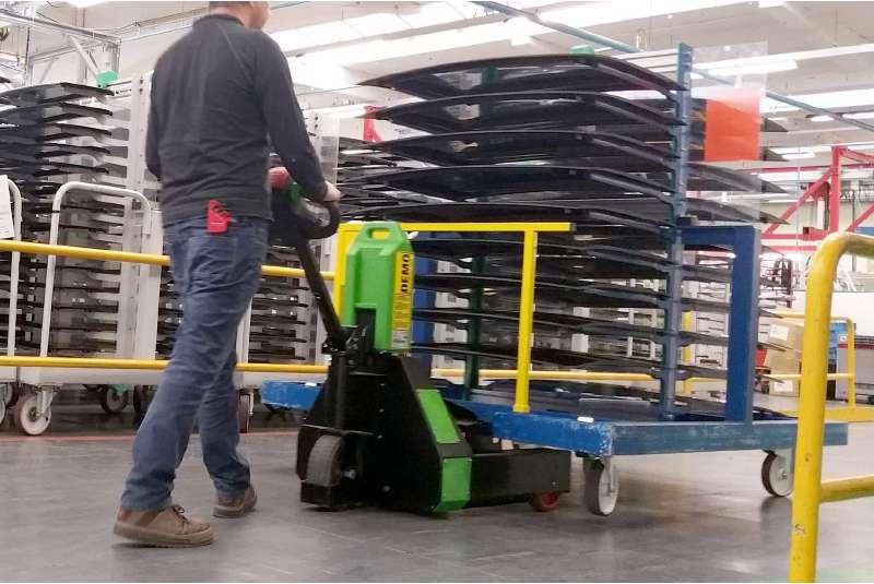 ručně vedený elektrický tahač t1000-rz v automobilovém průmyslu ve výrobě, sndaná manipulace vozíku na kolečkách, elektrickým zdvihem vozík na jedné straně přizvedne