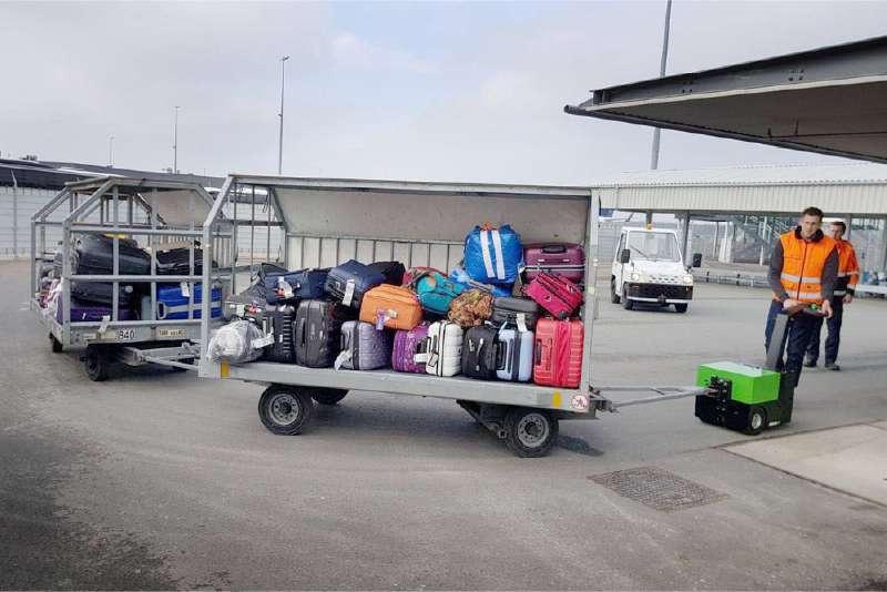elektrický ručně vedený tahač t2500 veze přívěsy se zavazadly spojené ojí na letišti