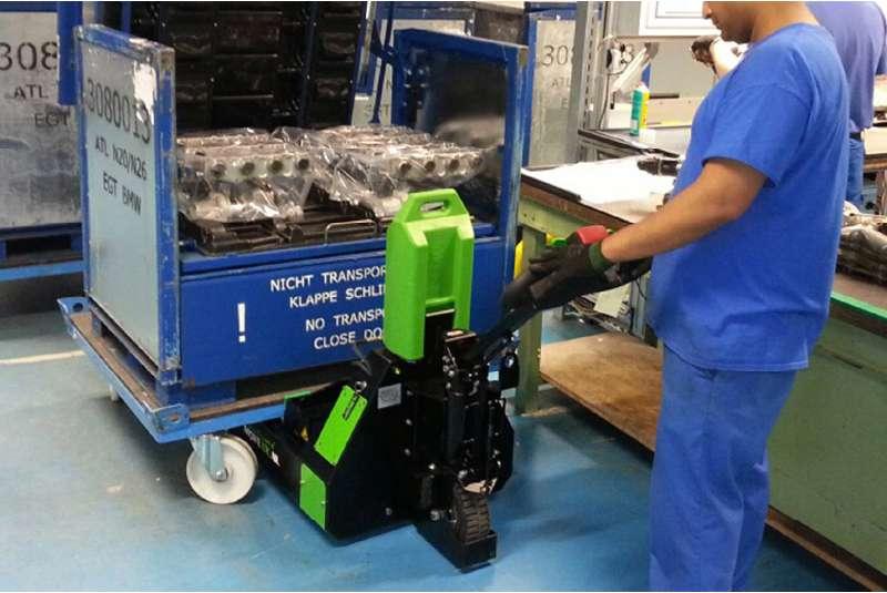 ručně vedený elektrický tahač t1000-rz elektrickým zdvihem přizvedne přepravní vozík, který má čtyři otočná kolečka