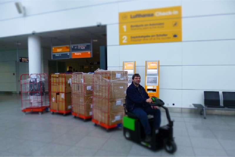 elektrický tahač t2500-scooter pro sedící obsluhu veze tažnou soupravu přepravních klecí na letišti