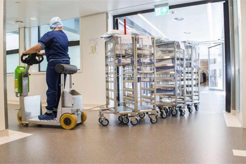 elektrický tahač t1000-platform rvs s plošinou pro stojícího řidiče veze soupravu přepravních vozíků po chodbě nemocnice