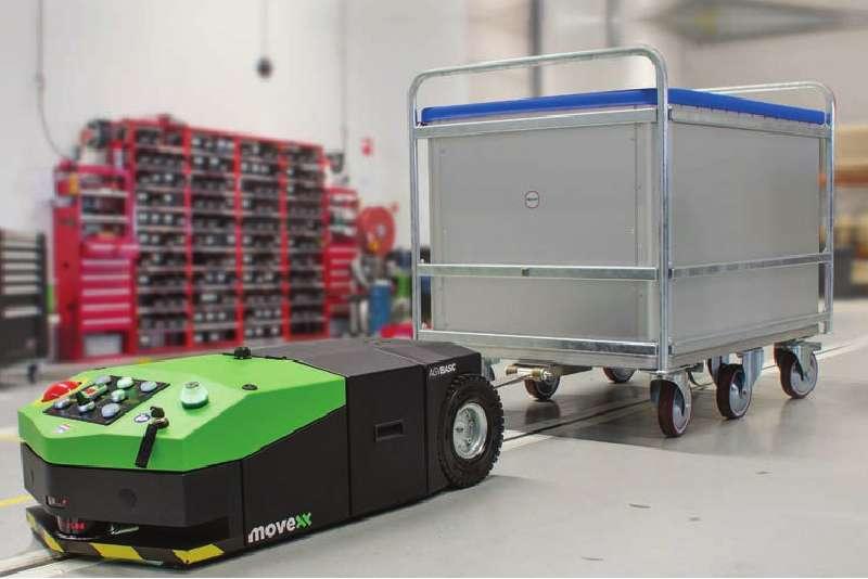 elektrický automaticky vedený tahač agv-basic veze přepravní vozík zapojený ojí po předem vyznačené trati při zásobování výroby, milkrun systém