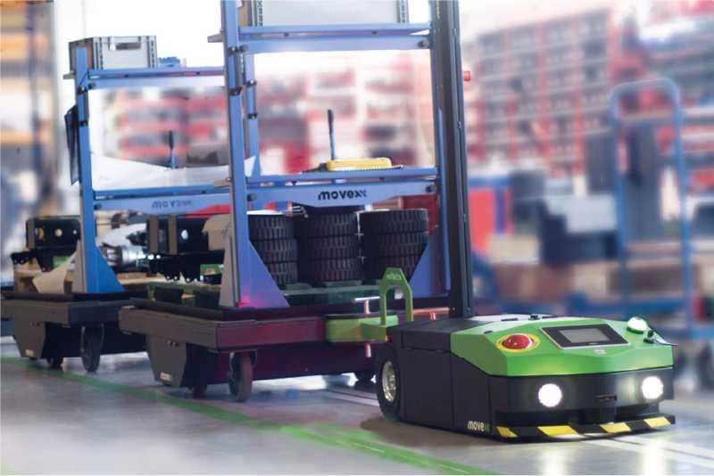 elektrický automaticky vedený tahač agv2500 s osvětlením a připojenou tažnou soupravou automaticky sleduje trasu a zásobuje výrobu