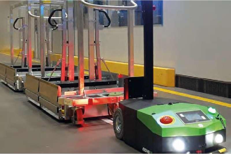 elektrický automaticky vedený tahač agv1000 má zapnuté osvětlení a jede se zapojenou milkrun tažnou soupravou naložit materiál do výroby