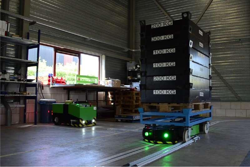 elektrický automaticky vedený tahač agv1000-underrider uchycený pod vozíkem a se zapnutým osvětlením veze materiál do výroby