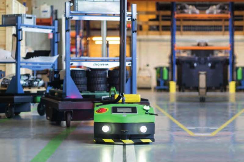 elektrický automaticky vedený tahač agv2500 s rozsvícenými světly veze tažnou soupravu k montážní lince při zásobování výroby