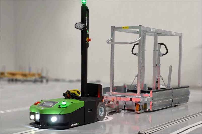 elektrický automaticky vedený tahač agv1000 veze přepravní vozík připojený ojí po značené trase směrem k montážní lince, automatické zásobování výroby milkrun systém