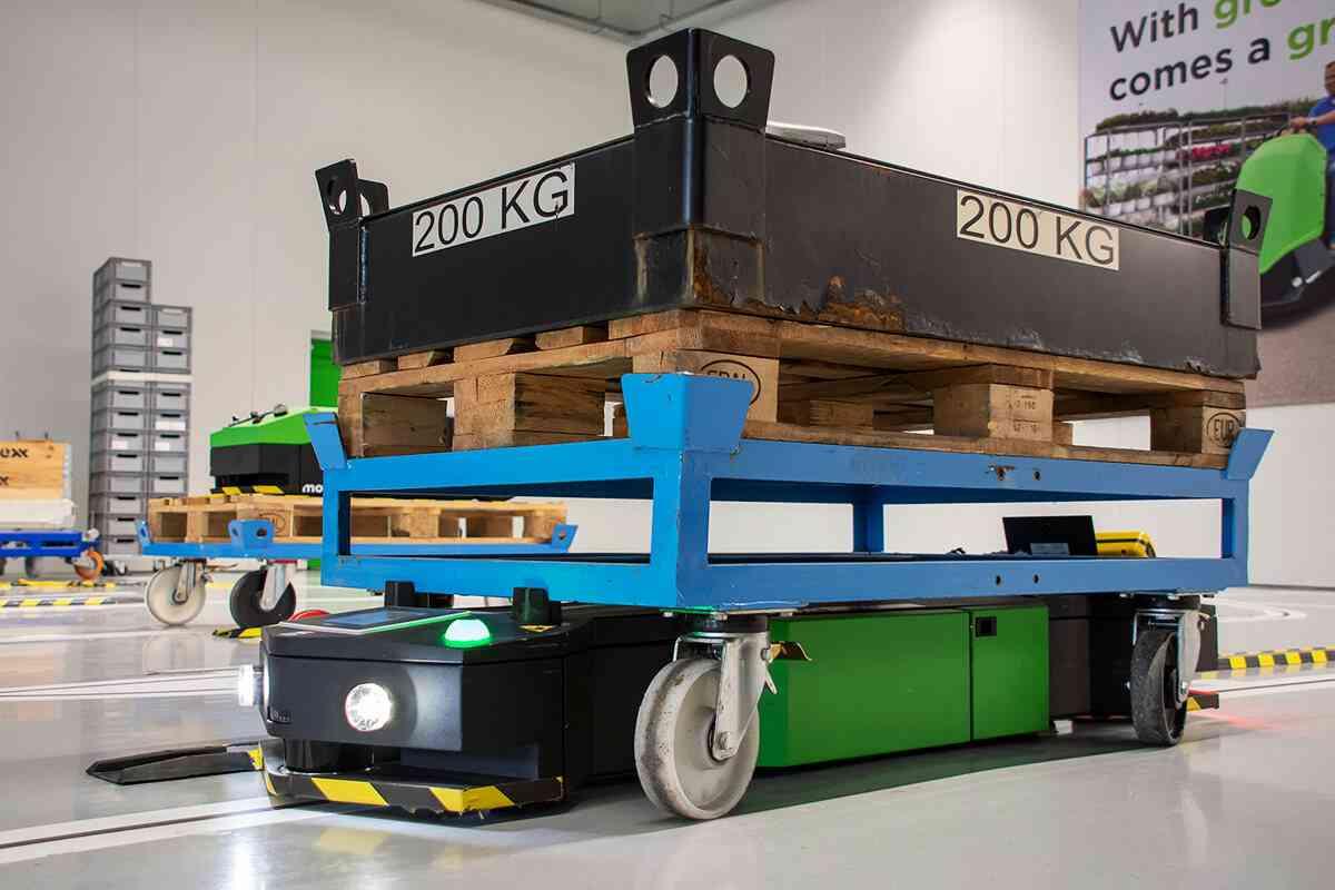elektrický automaticky vedený tahač agv1000-underrider se zapnutými světly jede po vyznačené trase pod uchyceným přepravním vozíkem