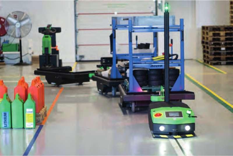 elektrický automaticky vedený tahač agv2500 jede skladem se zapřaženou tažnou soupravou naloženou materiálem do výroby při milkrun automatickém zásobování výroby