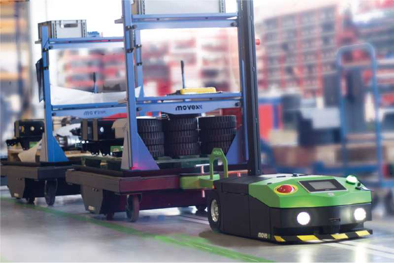 elektrický automaticky vedený tahač agv1000 se zapnutými světly veze tažnou soupravu s nákladem do výroby po vyznačené trase