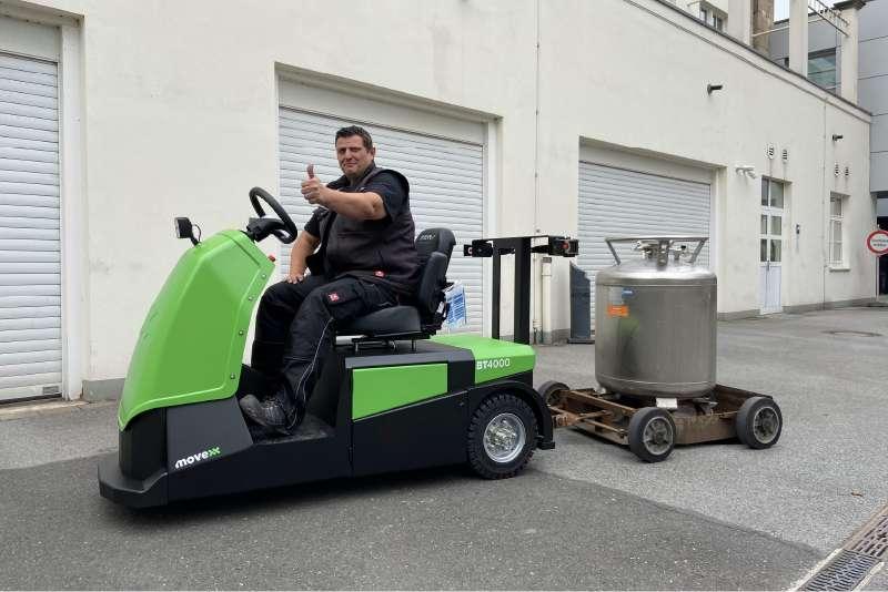 elektrický tahač bt4000 pro sedící obsluhu, ukázka venkovní manipulace, tahač má vzadu ojí připojený vozík s nákladem