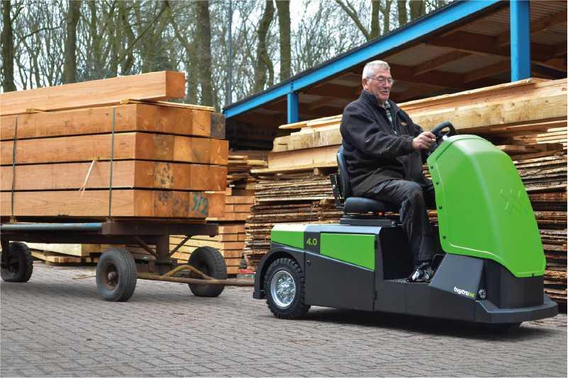 elektrický tahač bt4000 pro sedícího řidiče venku veze valník připojený ojí naložený dřevěnými trámy