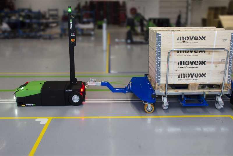 elektrický automaticky vedený tahač agv2500 ve skladu za sebou veze e-rámy při zásobování výroby milkrun tažnou soupravou
