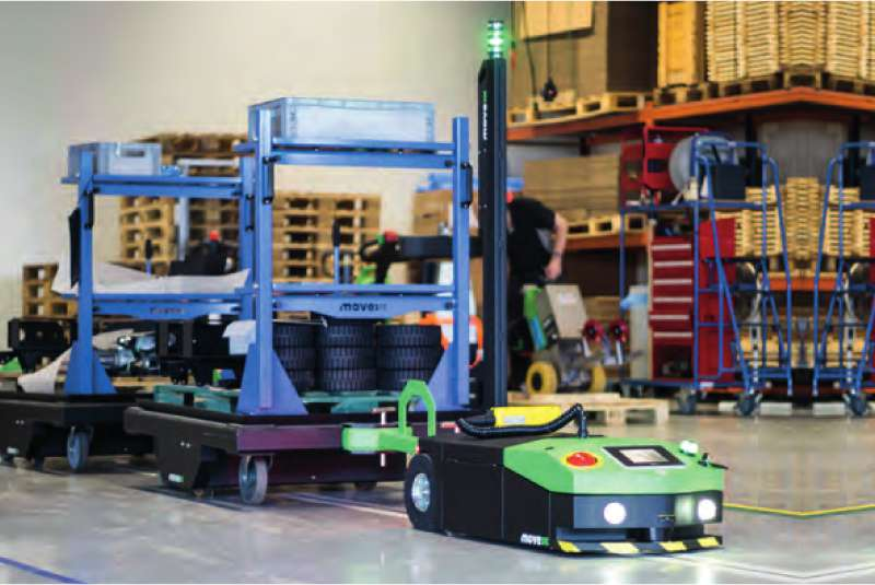 elektrický automaticky vedený tahač agv2500 veze ve skladu po vyznačené dráze tažnou soupravu milkrun s nákladem pro automatické zásobování výroby
