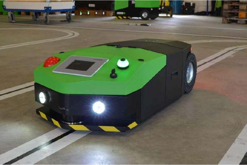 elektrický automaticky vedený tahač agv1000 se zapnutým osvětlením sleduje pomocí optické navigace vyznačenou trasu