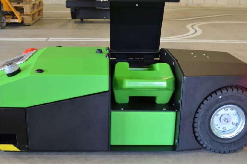 elektrický automaticky vedený tahač agv1000 ve skladu a jeho otevřený kryt z boku pro snadnou výměnu baterie