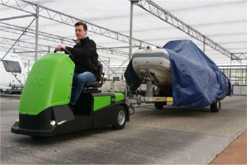 elektrický tahač bt4000 pro sedící obsluhu přepravuje venku přívěs s motorovým člunem