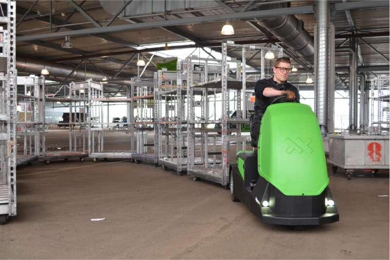 elektrický tahač bt4000 pro sedící obsluhu veze dlouhou tažnou soupravu policových vozíků uvnitř skladu