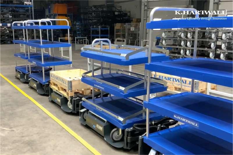 tažná souprava ve skladu, b rámy liftliner pro milkrun přepravu nákladu s vozíky elephant dolly